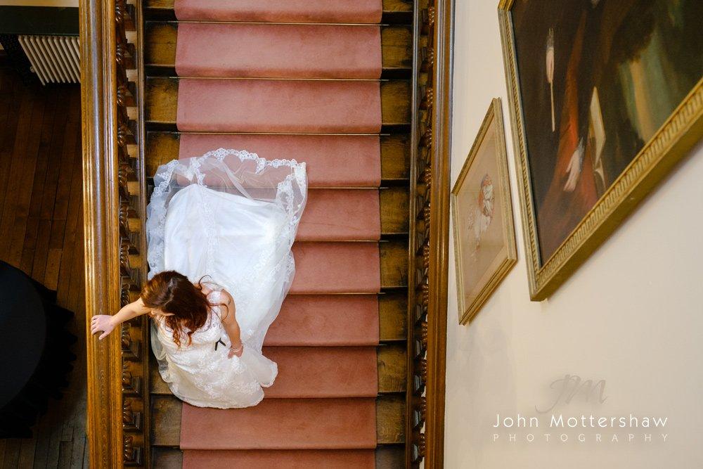 Bride walking downstairs at Arley Hall, Cheshire