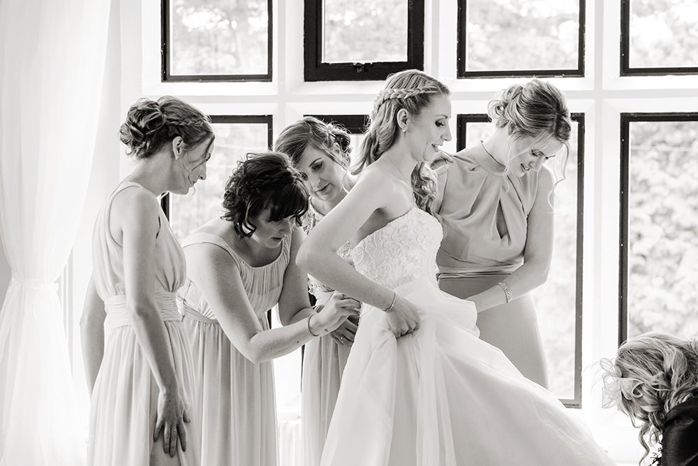 black and white of the bride putting her dress on