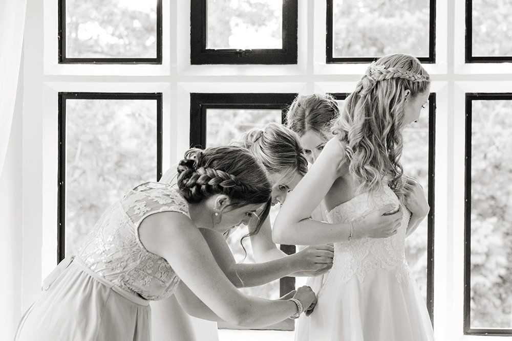 bridesmaids tying up the bride's dress