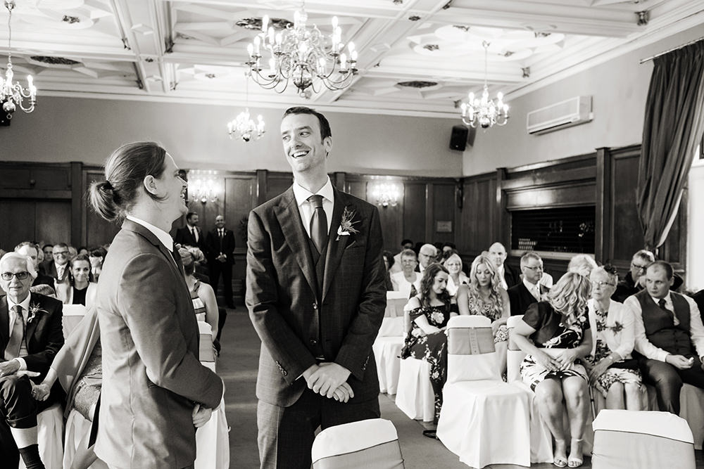 black and white photograph; a groom awaits the arrival of his bride