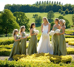 A bride talks to her bridesmaids in the gardens at her wedding at Hassop Hall near Sheffield, posing for their wedding photographs.