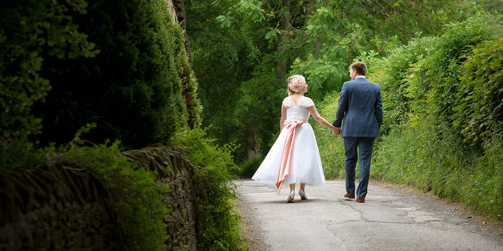 The bride and groom walk along the lane near Losehill House in the Derbyshire Peak District after their wedding. Natural reportage wedding photography.