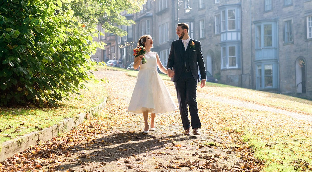 A bride and groom walk in the autumn sunshine heading towards the Old Hall Hotel in Buxton. The wedding was at Saint Ann's Church and photographed by Sheffield wedding photographer John Mottershaw.
