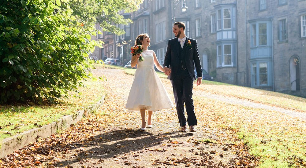 A bride and groom walk in the autumn sunshine heading towards the Old Hall Hotel in Buxton, near Sheffield. The wedding was at Saint Ann's Church and photographed by Sheffield wedding photographer John Mottershaw.