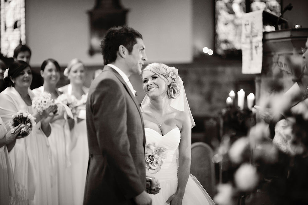 Black and white wedding photography at Bakewell Church in Derbyshire. An atmospheric winter wedding photograph showing the bride's happiness, by wedding photographer John Mottershaw.