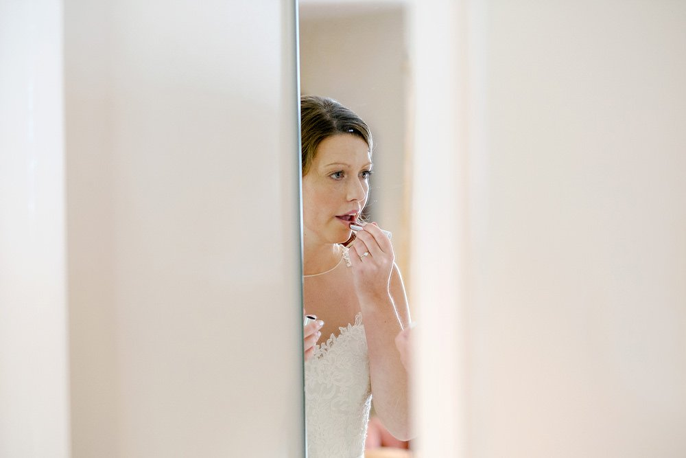 A bride applies her make up in a mirror at Losehill House in Derbyshire.
