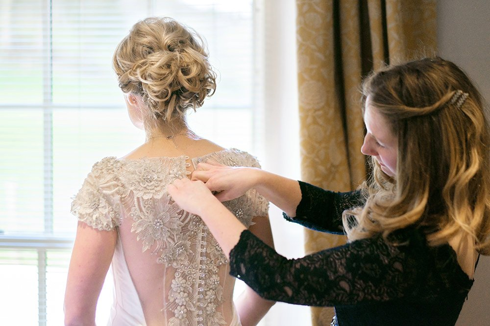 a bride's dress is fastened for her wedding at Losehill House in the Peak District