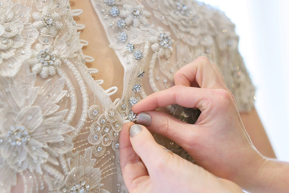Buttoning up the bride's dress for her wedding at Losehill House