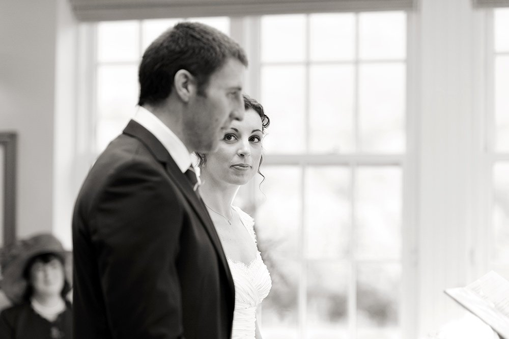 A bride looks at her groom during their wedding ceremony in black and white