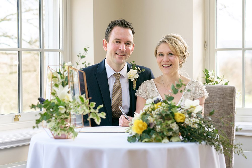 A happy couple sign the register at their civil wedding at Losehill House in the Derbyshire Peak District
