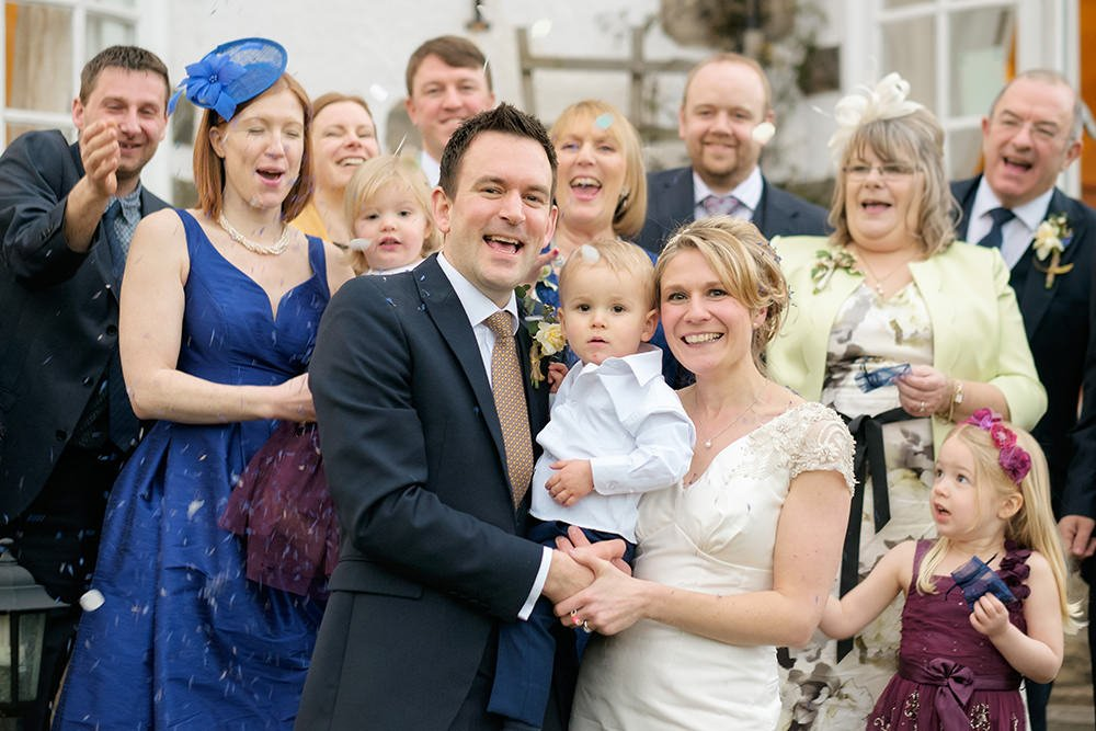Happy and informal wedding photography of a group throwing confetti at the bride and groom