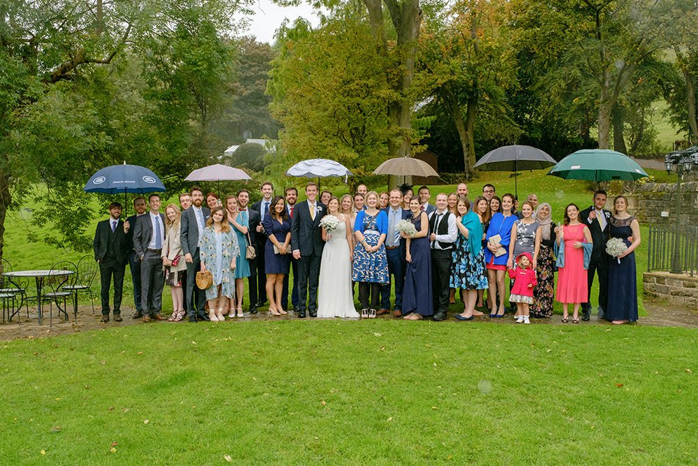 wedding guests pose for their group photograph with umbrellas at Losehill House