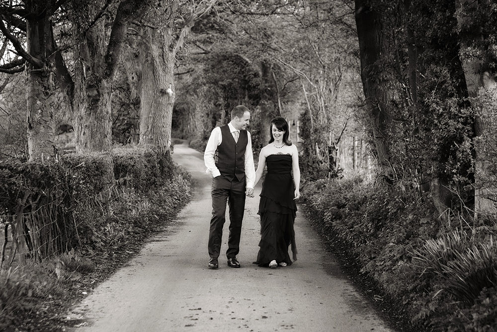 wedding photograph in black and white of a bride and groom walking along a lane in Derbyshire Peak District