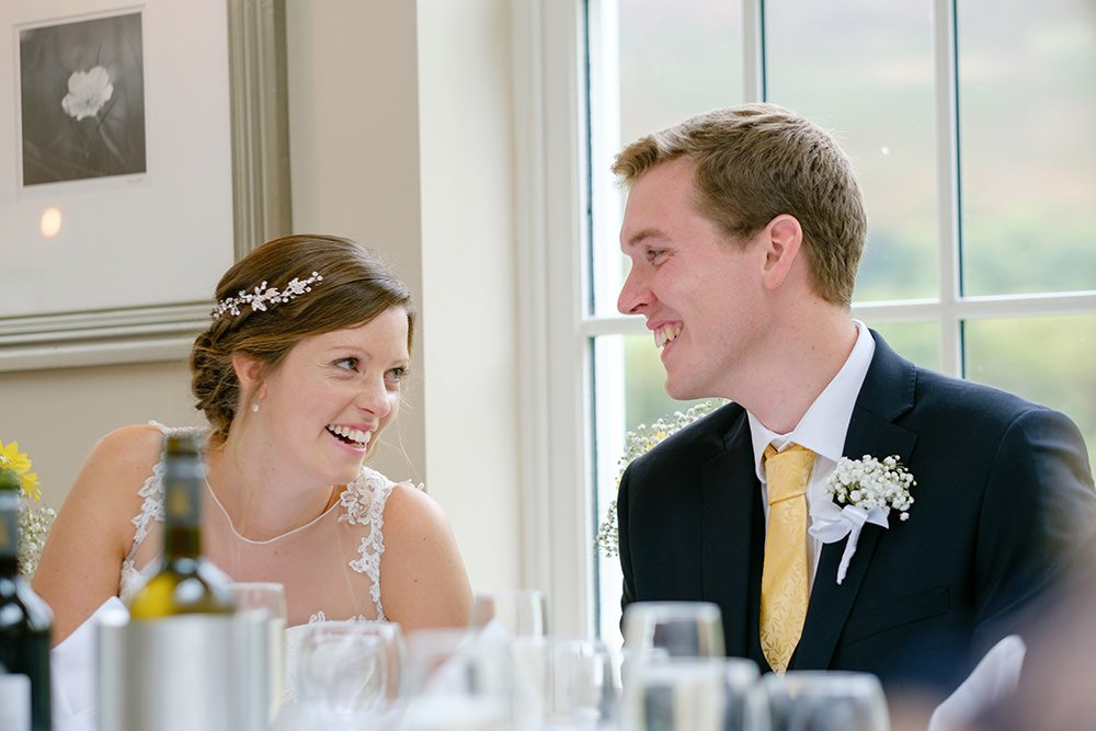 The bride and groom laugh together at speeches at their wedding at Losehill House