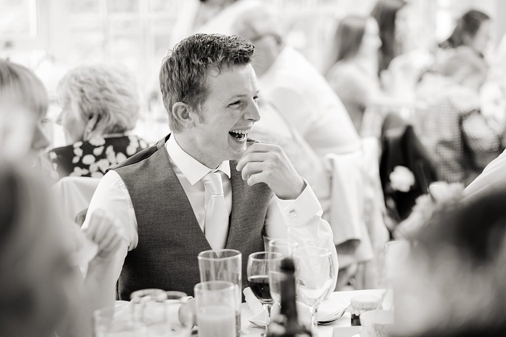 Black and white wedding photography of wedding guest laughter at speeches