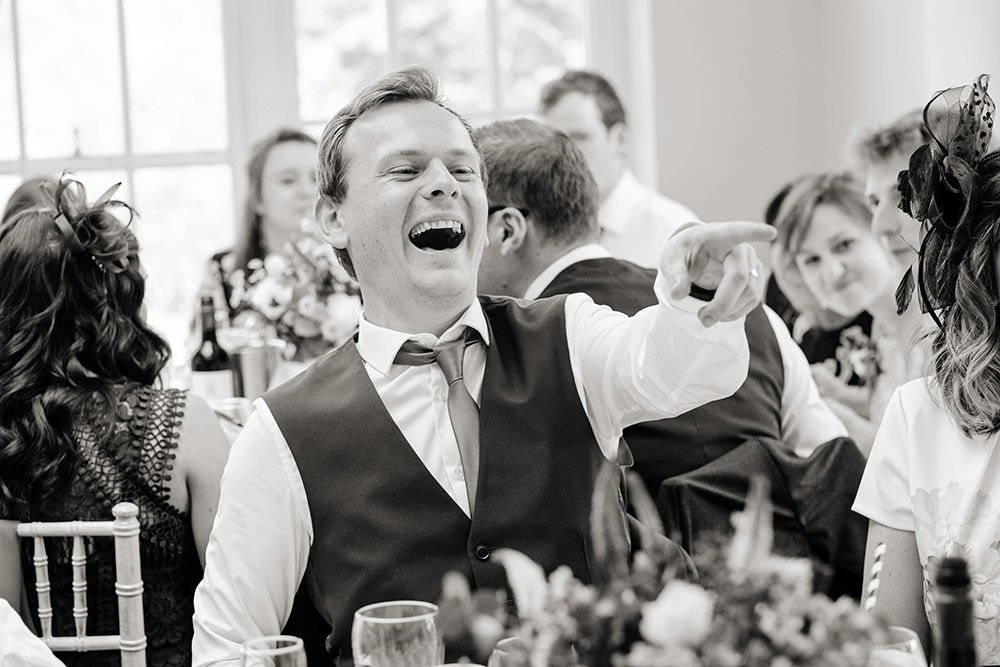 A wedding guest laughs at the speeches