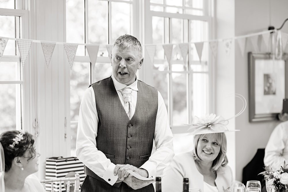 The father of the bride gives his speech. Wedding photography in black and white.