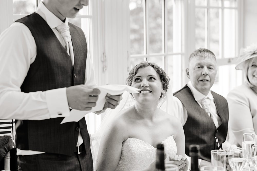 The bride looks on at her groom as he makes his speech at Losehill House
