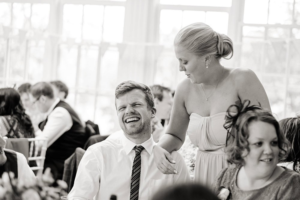 Black and white wedding photograph of laughter at the speeches