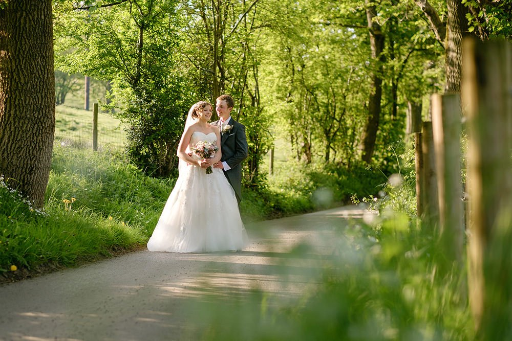 A bride and groom enjoy their wedding at Losehill House near Sheffield, a venue with beautiful views of the hills of the Peak District. Photography by Sheffield wedding photographer in a rural lane by Losehill.