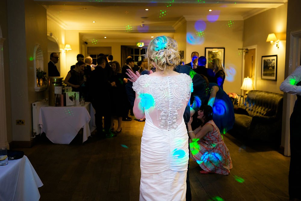 a bride looks on as her wedding guests enjoy dancing