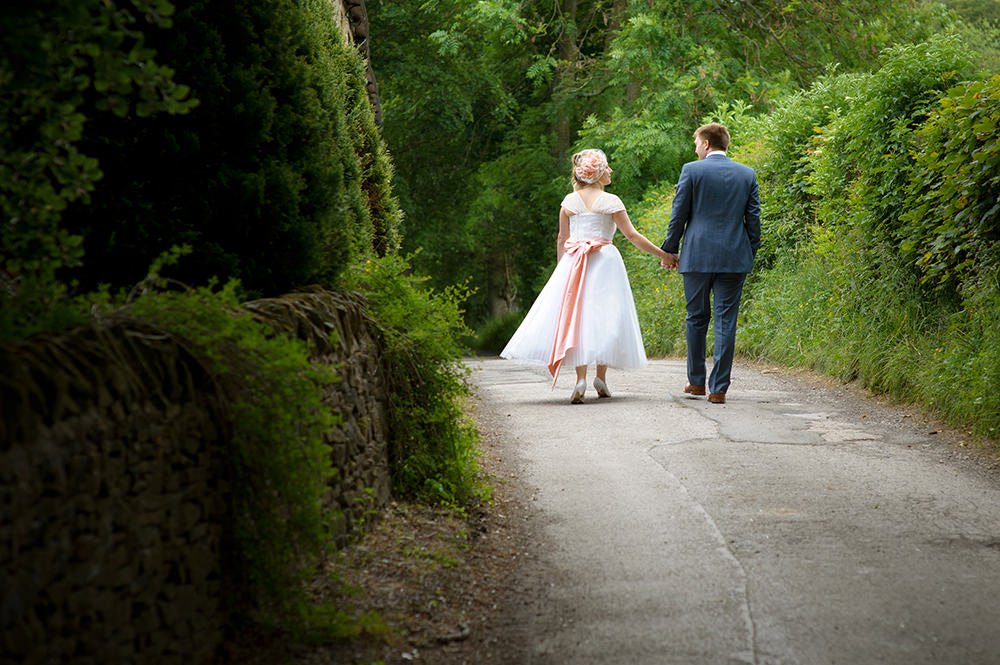 A newly married couple walk along the lane near Losehill House in Derbyshire