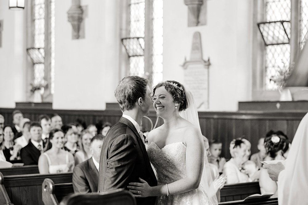 Black and white wedding photograph of the first kiss at a wedding at Taxal Church in Derbyshire. Captured by Sheffield photographer John Mottershaw.
