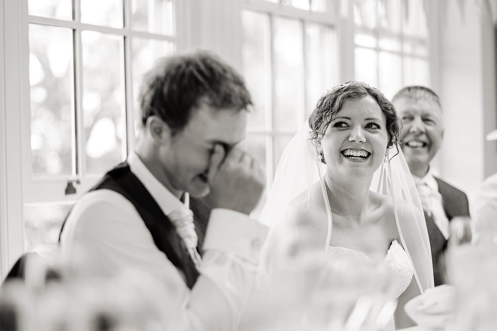 The bride laughs at best man's speech at a wedding at Losehill House, near Sheffield. Black and white wedding photography.
