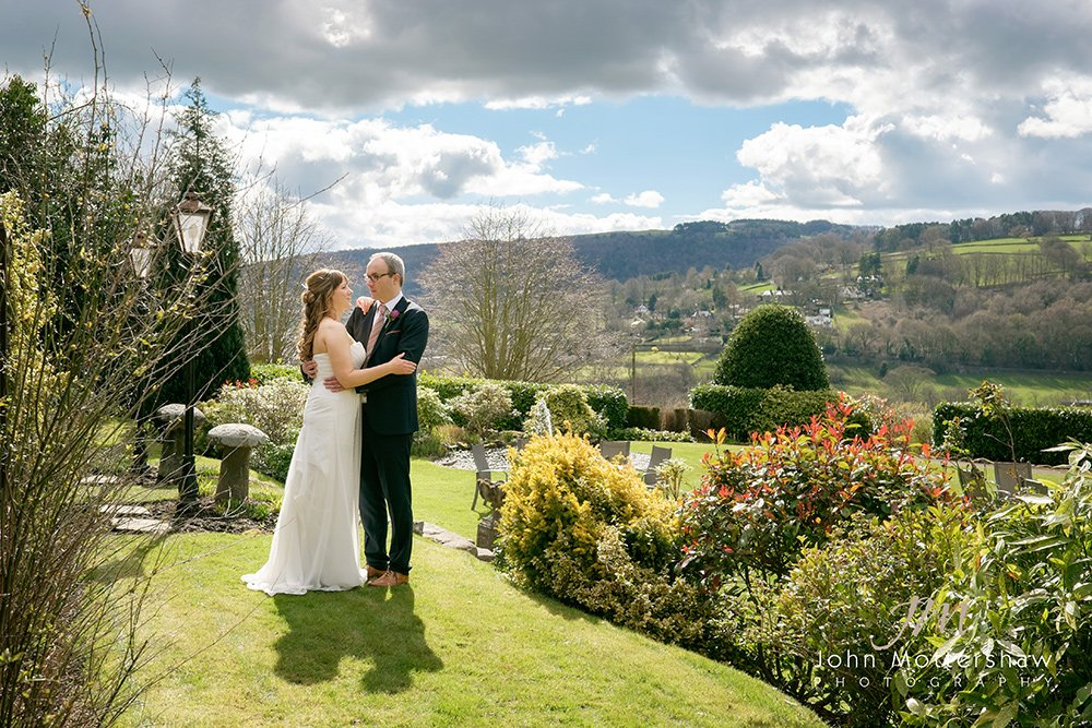 A bride and groom enjoy their wedding at the Maynard near Sheffield, with beautiful views of the hills of the Peak District behind. Photography by Sheffield wedding photographer in the gardens of the Maynard.