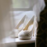 A bride's shoes seen through the edge of her wedding dress, before a wedding at the Maynard by Sheffield wedding photographer John Mottershaw.