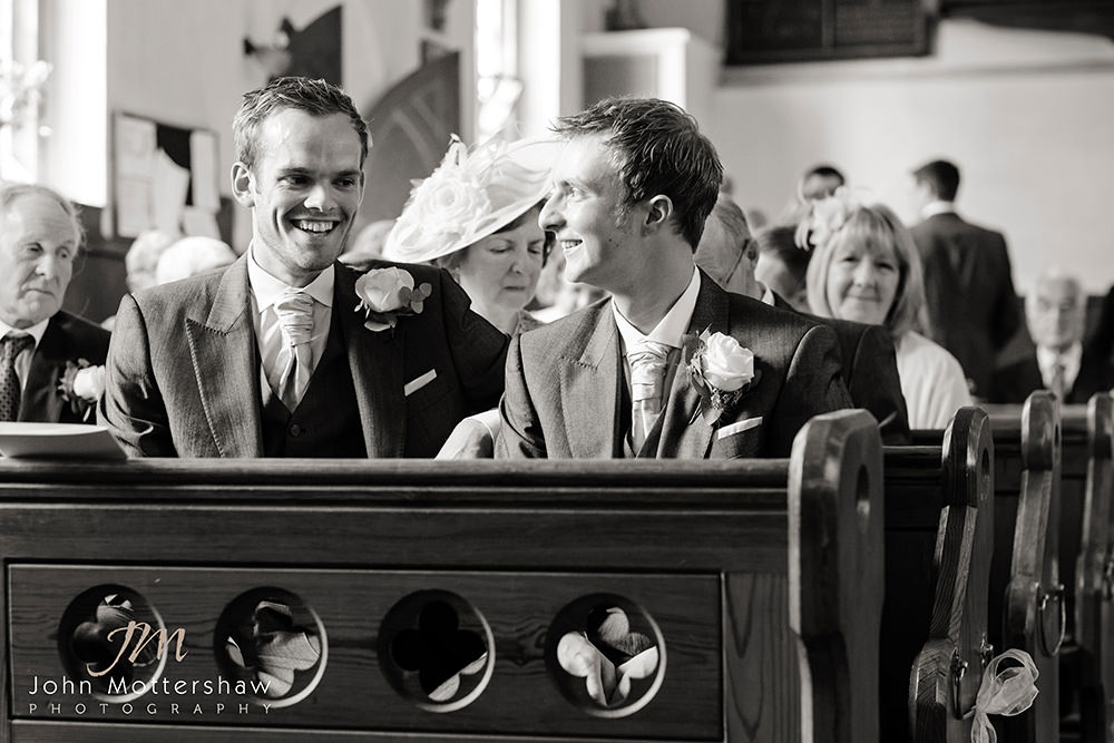 Wedding photography in black and white of a groom and best man in Taxal Church awaiting his bride