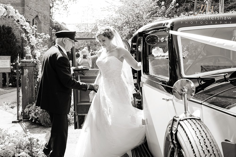 bride arrives at a wedding at Taxal Church near Cheshire. Black and white image by Sheffield wedding photographer John Mottershaw.