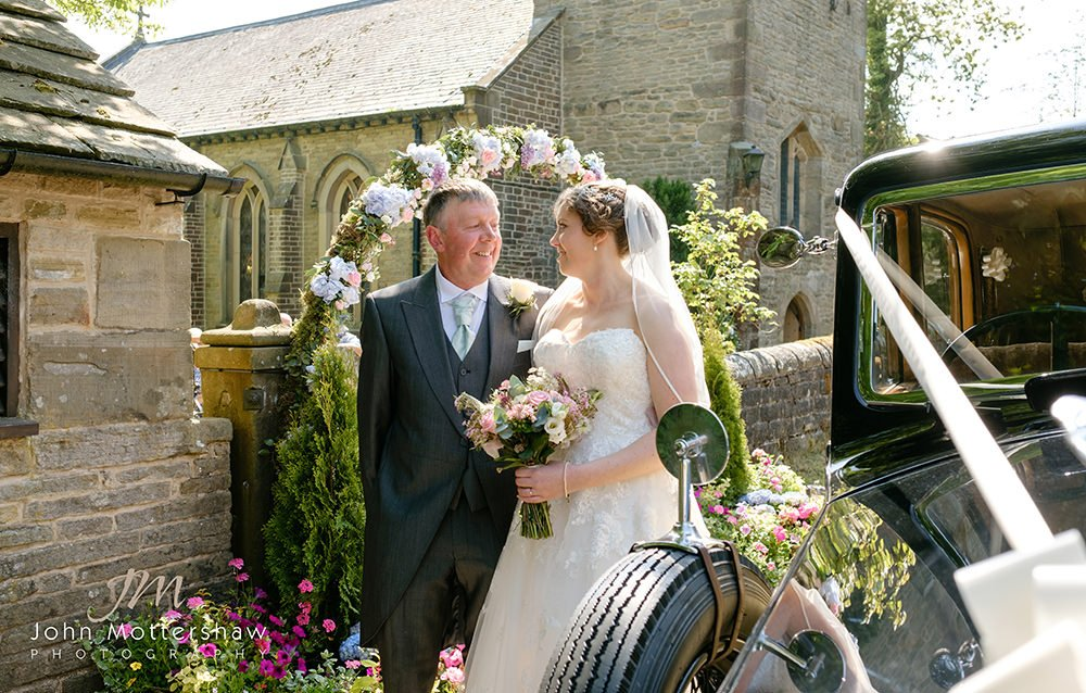 bride and her father arrive at a wedding at Taxal Church near Cheshire by Sheffield wedding photographer John Mottershaw.