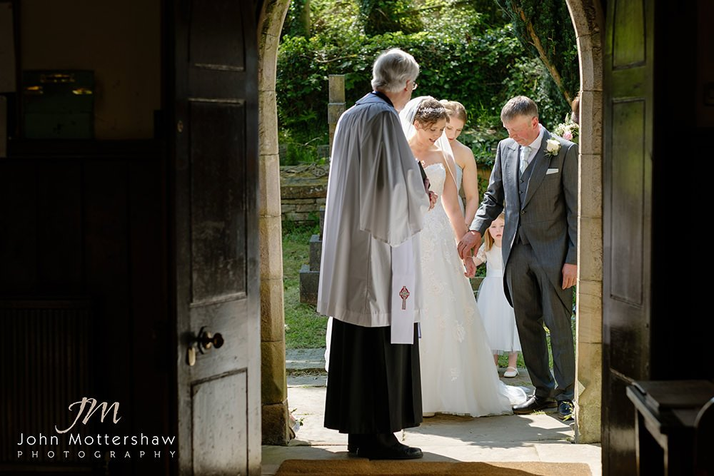 the bride, her father and bridesmaids are at the door of Taxal Church ready to enter the wedding