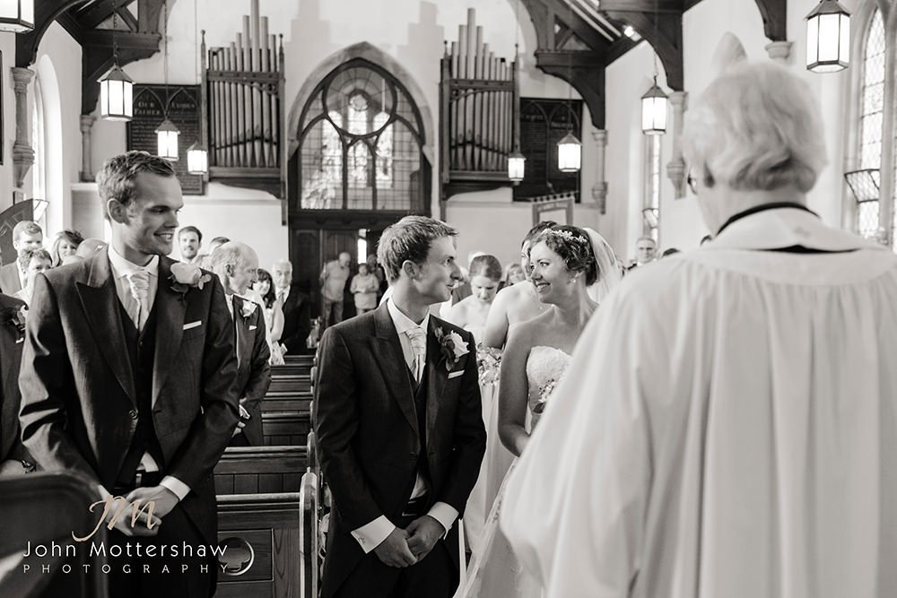 bride and groom at their rural church wedding ceremony. The best man looks on. By Sheffield wedding photographer John Mottershaw.