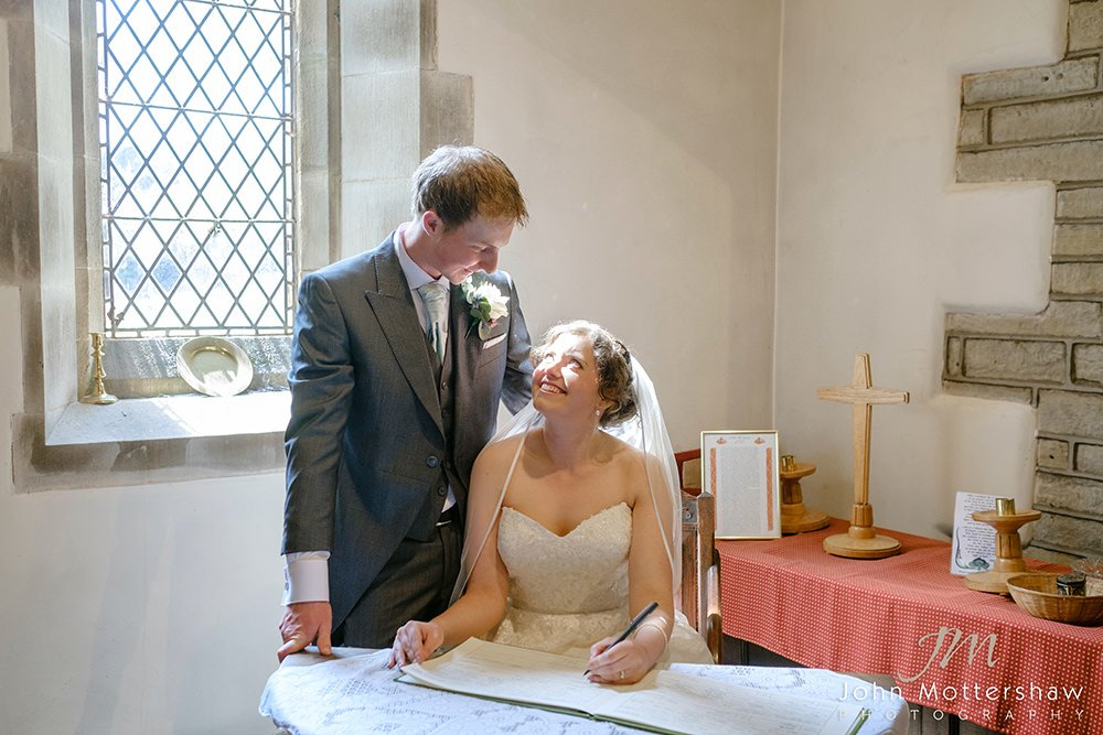bride and groom sign the register at their Cheshire church wedding