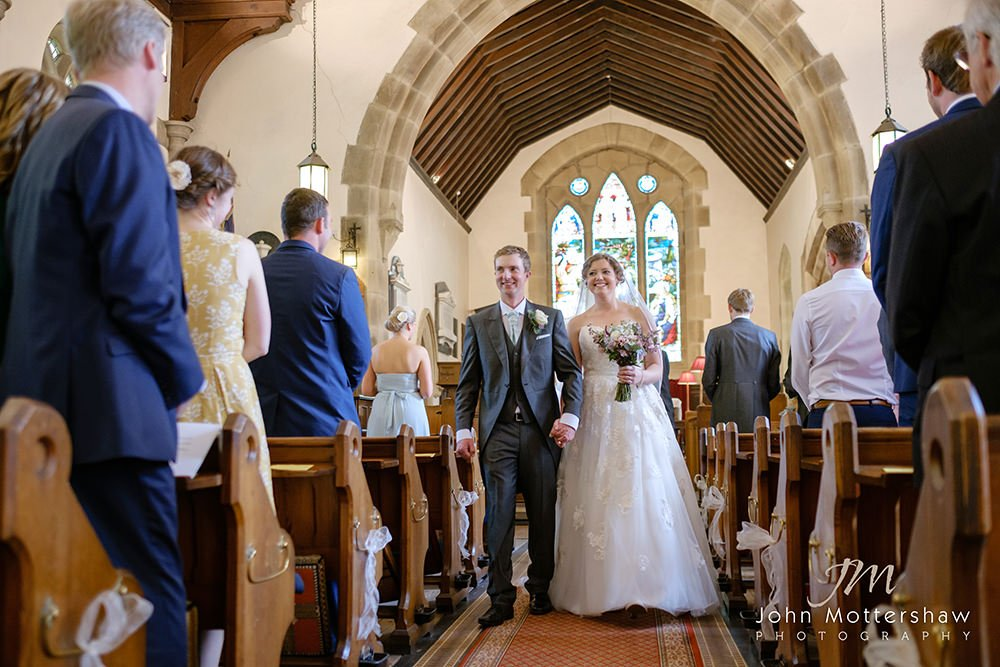 bride and groom walk down the aisle as they leave their Cheshire church wedding