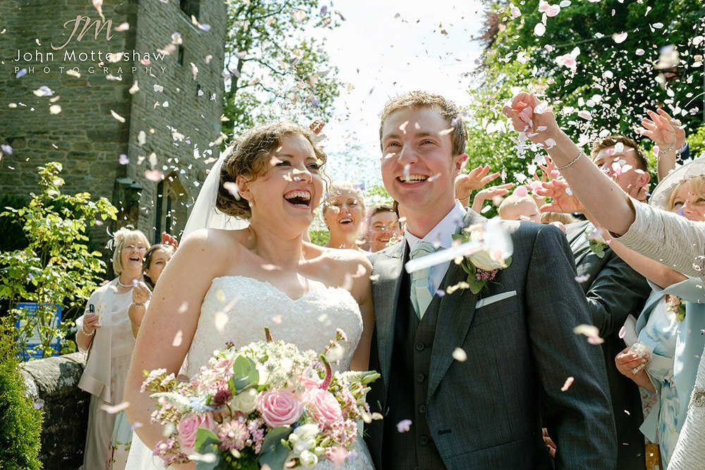 lively confetti shot at a wedding at Taxal Church. Wedding photography in Derbyshire.