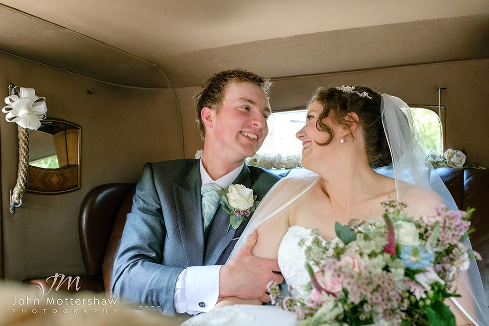 Wedding photographer photographs smiles of the bride and groom in the back of a vintage Rolls Royce