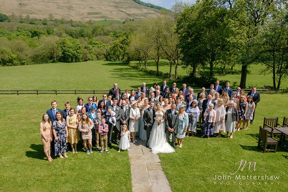 Sheffield wedding photographer at Losehill House. A large group shot with hills in the background.