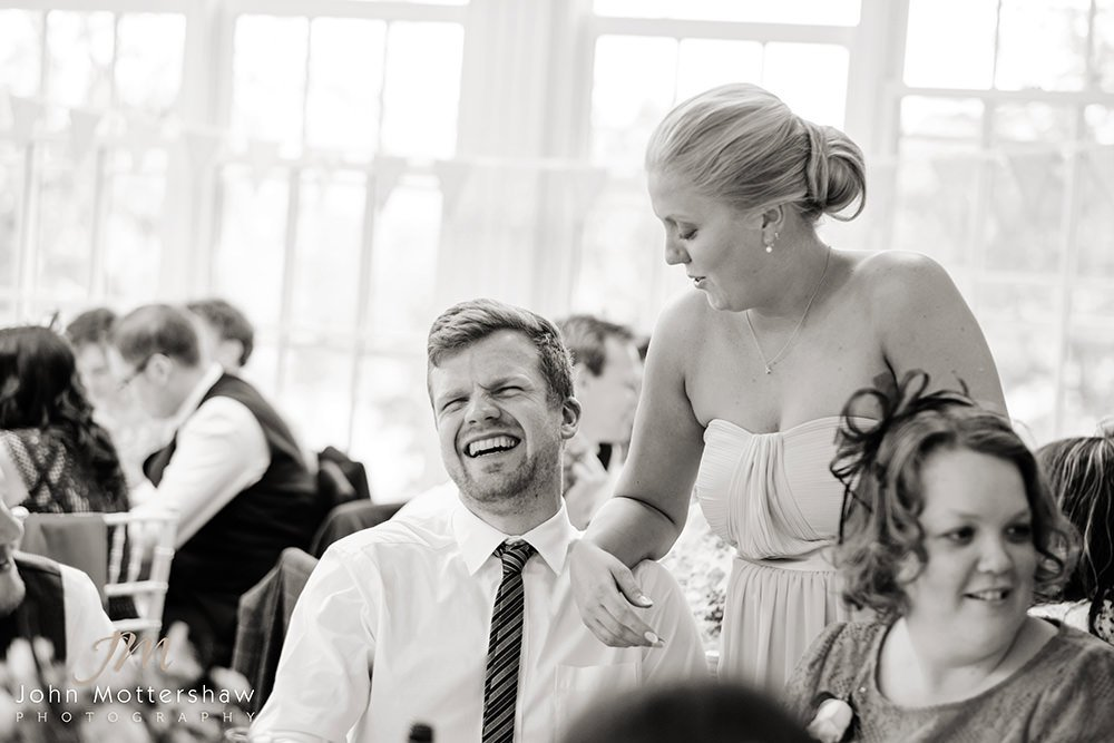 Black & white wedding photograph of guests laughing together at this wedding near Sheffield