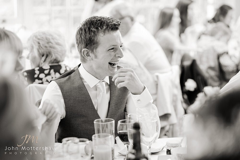 Black & white wedding photograph of guest laughing at this wedding near Sheffield