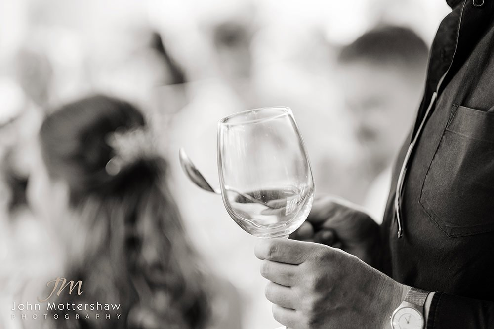 Black & white wedding photograph of tapping a glass to announce the speeches
