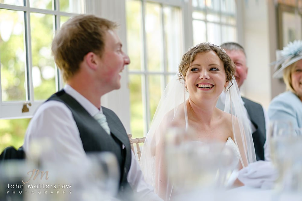 The bride laughs at the best man's speech at this wedding at Losehill House in the Peak District