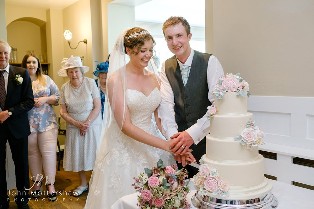 Bride and groom cut the cake at a Peak District wedding, whilst relatives look on.