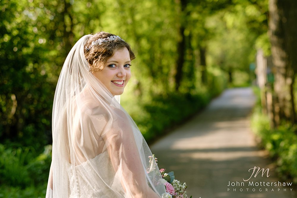 a bride on a country lane near Losehill House in the Peak District