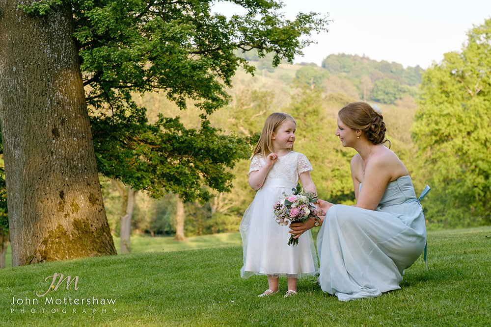 gentle informal wedding photography at Losehill House of a bridesmaid talking to a flower girl