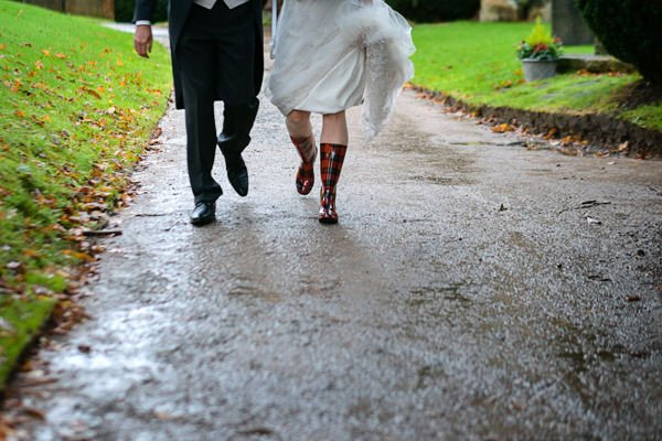 The bride and groom walking up the church path. The bride is wearing wellies.