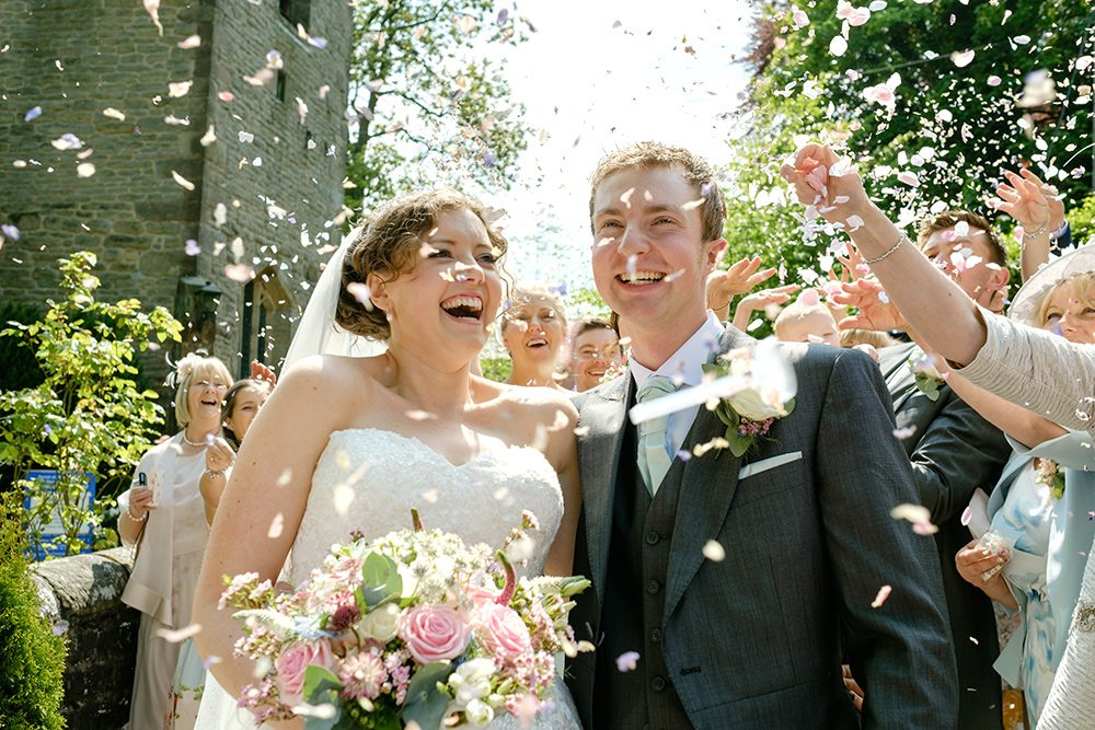 Confetti thrown at a bride and groom after their Cheshire wedding at Taxal Church. The wedding reception was later held at Losehill House.