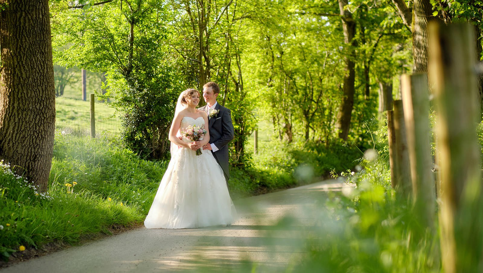 After their wedding at Taxal Church, a bride and groom admire each other in the evening sunlight on the lane at Losehill House. A perfect location in the Peak District for their Sheffield wedding photographer.